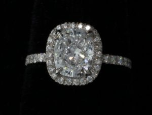 Platinum Jewelry - A large circular cut diamond surrounded by smaller diamonds in a platinum setting.