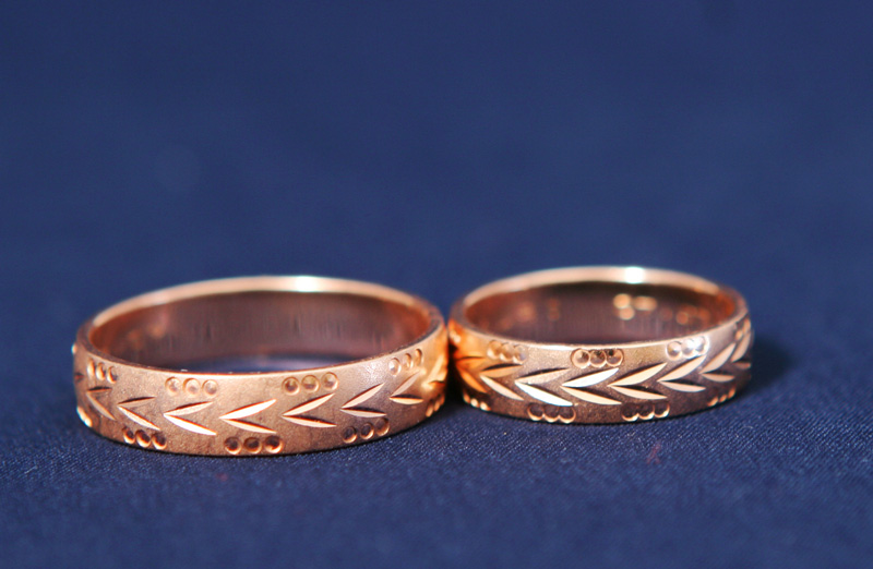 two rosegold rings with ornate carvings