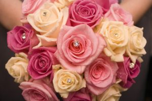 Detail of a bouquet of pink and peach colored roses. Several roses have shimmering diamonds nestled in their centers.