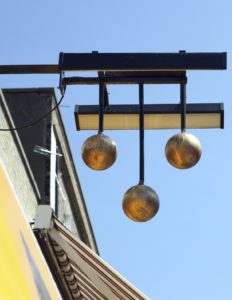 The famous three gold balls sign of a pawnbroker's shop, above a street in Great Yarmouth, Norfolk, eastern England.