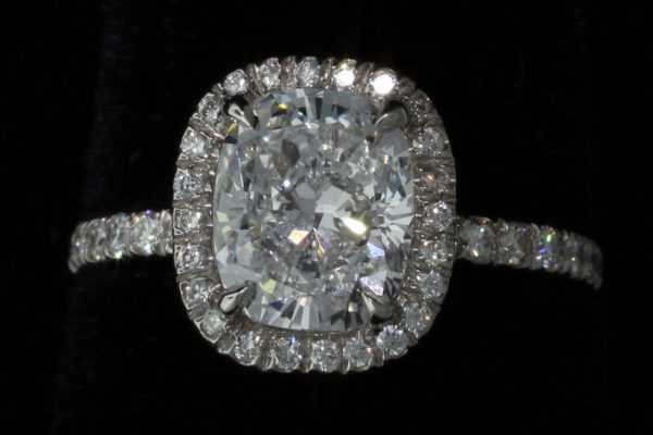 ring with a large central diamand and several round ut diamonds in a platinum setting